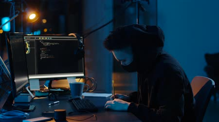 estatísticas : hacker in mask using computers for cyber attack Stock Footage