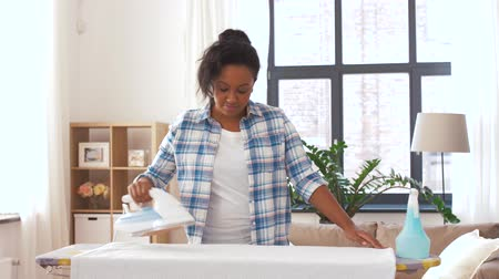 püskürtücü : african american woman ironing bed linen at home Stok Video