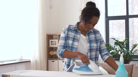 çamaşırhane : african american woman ironing bed linen at home Stok Video