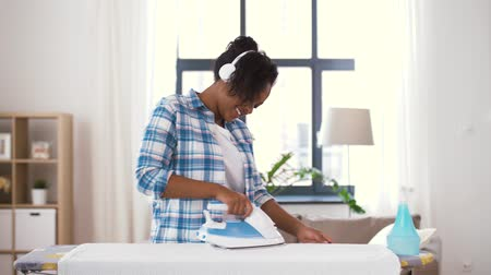 lavanderia : african american woman ironing bed linen at home Stock Footage