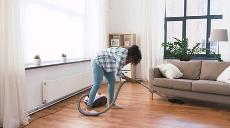 odkurzacz : african american woman with vacuum cleaner at home Wideo
