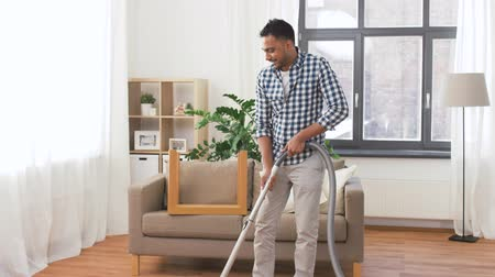 trabalhos domésticos : man with vacuum cleaner at home Stock Footage