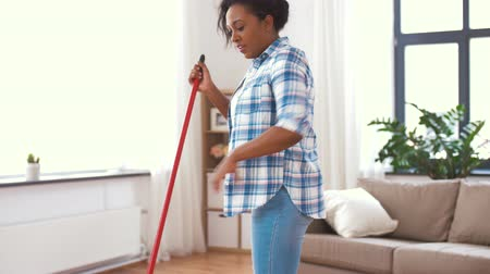 süpürge : woman with sweeping broom brush cleaning floor Stok Video