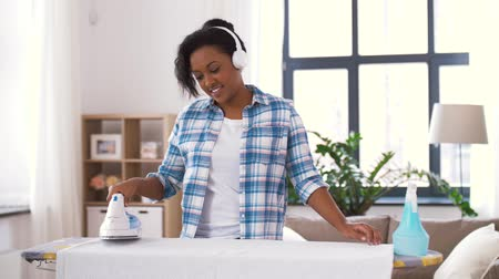 spraying : african american woman ironing bed linen at home Stock Footage