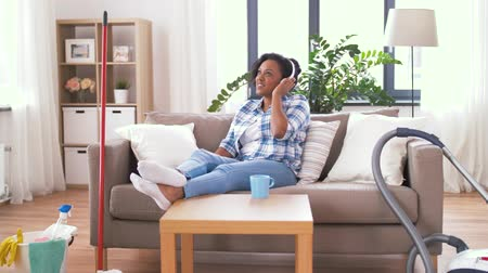 playlist : woman in headphones resting after home cleaning Stock Footage