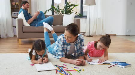 leisure time : mother with little daughters drawing at home