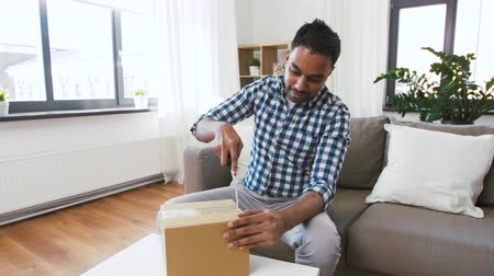 creator : male video blogger opening parcel box at home Stock Footage
