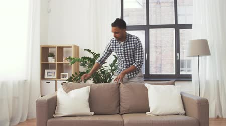 arranging : indian man arranging sofa cushions at home