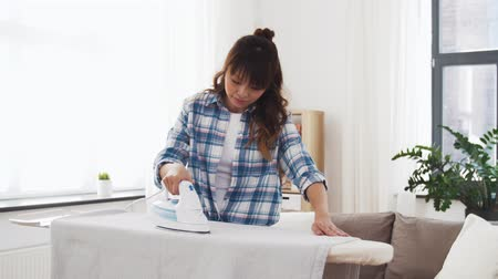 žehlení : asian woman ironing bed linen at home
