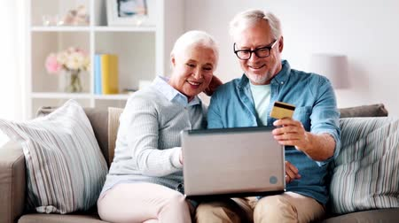 cash free : happy senior couple with laptop and credit card