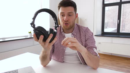 тестирование : male blogger with headphones videoblogging at home