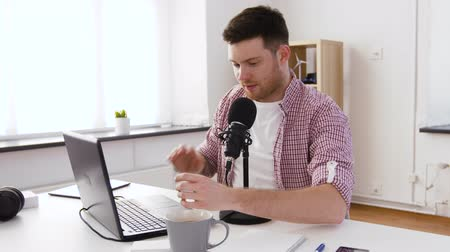 personal computers : happy young man with laptop and microphone at home