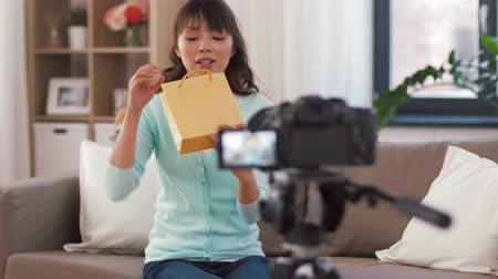 creator : asian female blogger with gift bag recording video