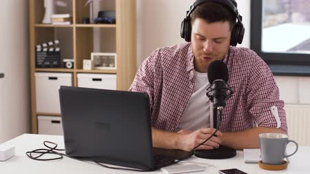 omroep : man in headphones with laptop speaks to microphone Stockvideo