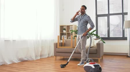 playlist : man in headphones with vacuum cleaner at home