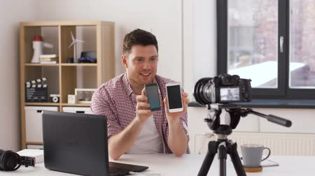 creator : male blogger with smartphone videoblogging at home