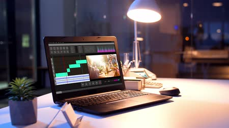 bureaulamp : video-editorprogramma op laptop 's nachts op kantoor Stockvideo