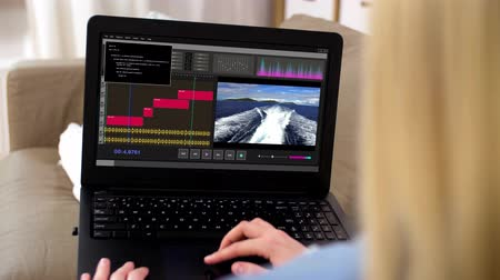 mixer : woman with video editor program on laptop at home