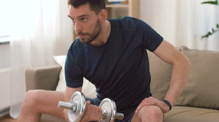 biceps curls : man exercising with dumbbells at home