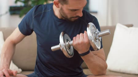 weightlifting : man exercising with dumbbells at home