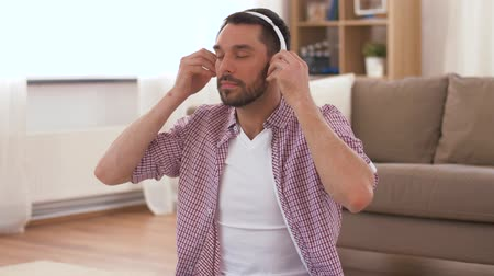 отступление : man in headphones meditating in lotus pose at home