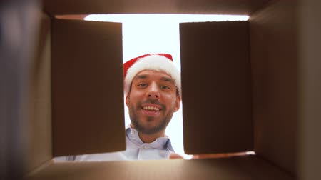 x mas : happy man opening parcel box or christmas gift