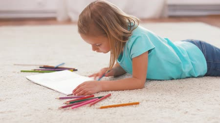 przedszkolak : girl drawing with crayons in sketchbook at home