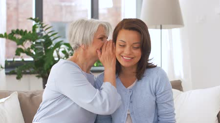 whispering : senior mother talking to adult daughter at home Stock Footage