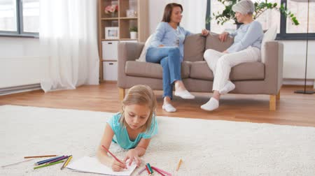 home grown : adults talking and girl drawing at home