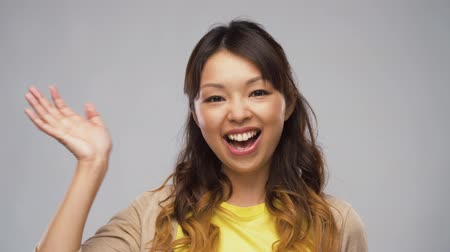 hallo : smiling asian woman waving hand