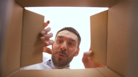 presentes : happy man opening parcel box with smartphone