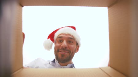 within : happy man opening parcel box or christmas gift