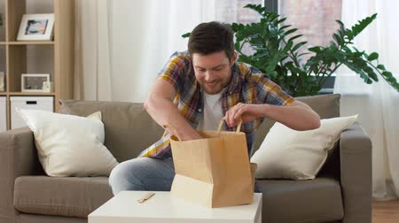 consumo : smiling man unpacking takeaway food at home Vídeos