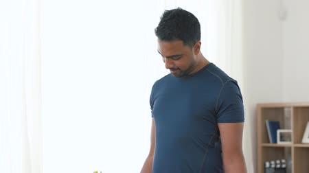 vzpírání : indian man exercising with dumbbells at home
