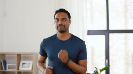 fitness tracker : man with wireless earphones exercising at home Stock Footage
