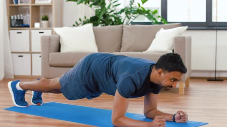 heart rate : man with fitness tracker doing plank at home