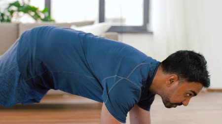 fitness tracker : man with fitness tracker doing plank at home