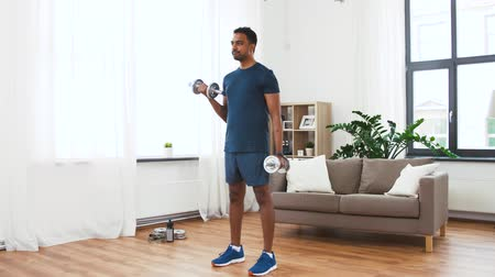 weight training : indian man exercising with dumbbells at home