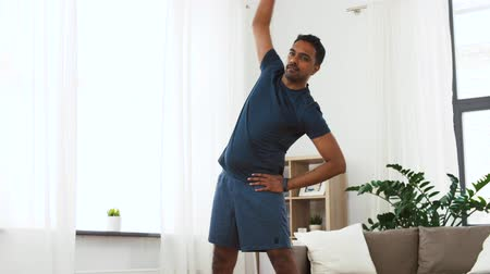 fitness tracker : indian man exercising and leaning at home Stock Footage
