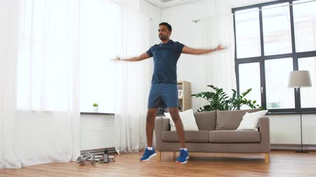 cardio : indian man doing jumping jack exercise at home