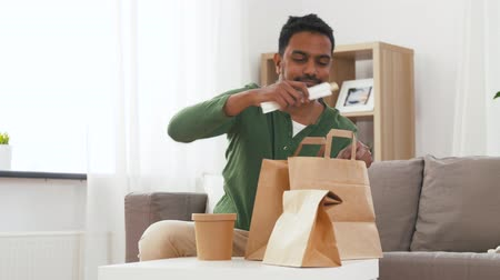 south asian food : smiling indian man unpacking takeaway food at home