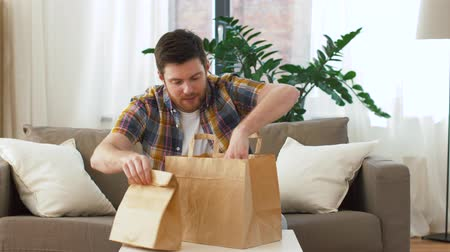 smelling : smiling man unpacking takeaway food at home Stock Footage