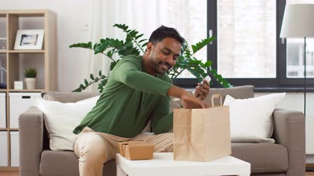 south asian food : indian man checking takeaway food order at home