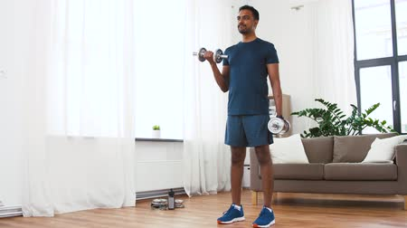 biceps curls : indian man exercising with dumbbells at home