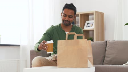 clientes : indian man with takeaway coffee and food at home Vídeos