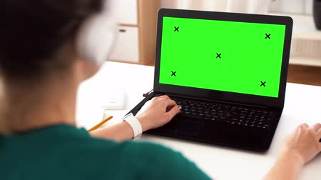 creator : woman with with green screen on laptop at home