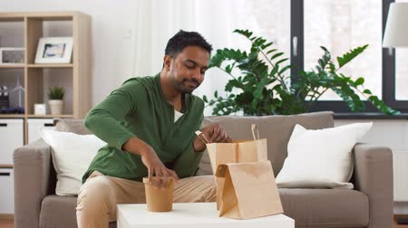 consumo : smiling indian man unpacking takeaway food at home