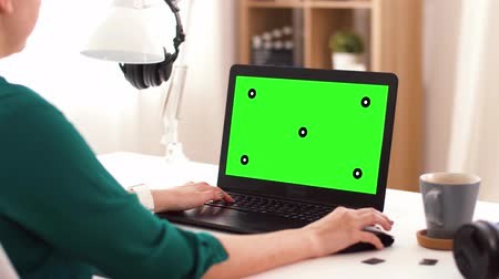creator : woman with green screen on laptop at home
