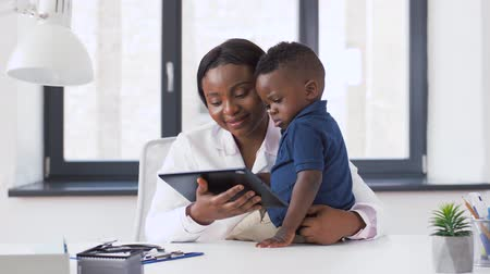 paediatrician : doctor showing tablet pc to baby patient at clinic