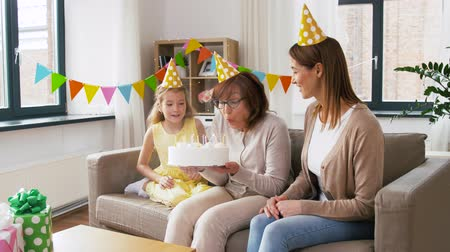 teen age : mother, daughter, grandmother with birthday cake